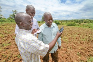 Asuman, left, measures his fields with a GPS device and help from Regional Agricultural Supervisor John Peter Emoi, center, and fellow farmer Joseph Mulandya. Courtesy: Opportunity Int'l.
