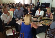 """Summit participants, including Randy Oostra (left) and Lee Hammerling, MD, (second from left) discuss the tie between hunger and obesity, stigmas of food insecurity and the role of healthcare during the """"meeting in a box"""" group activity. (Courtesy: ProMedica)"""